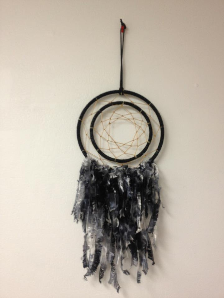 Hand made dreamcatcher comprised of leather, feathers, imitation sinew, beads, and charms