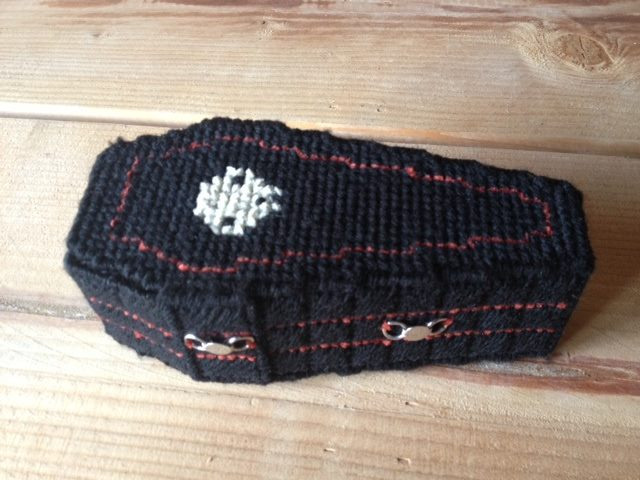 Coffin trinket box made out of yarn, plastic canvas, and metal charms or fasteners. Halloween inspired.